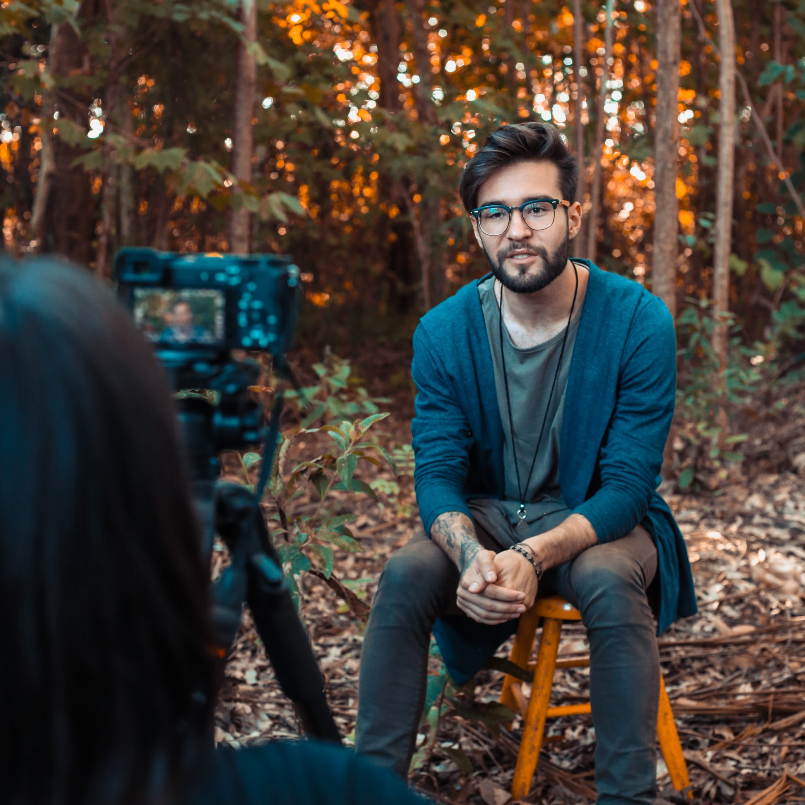 Professional video producer filming an interview in woodland.